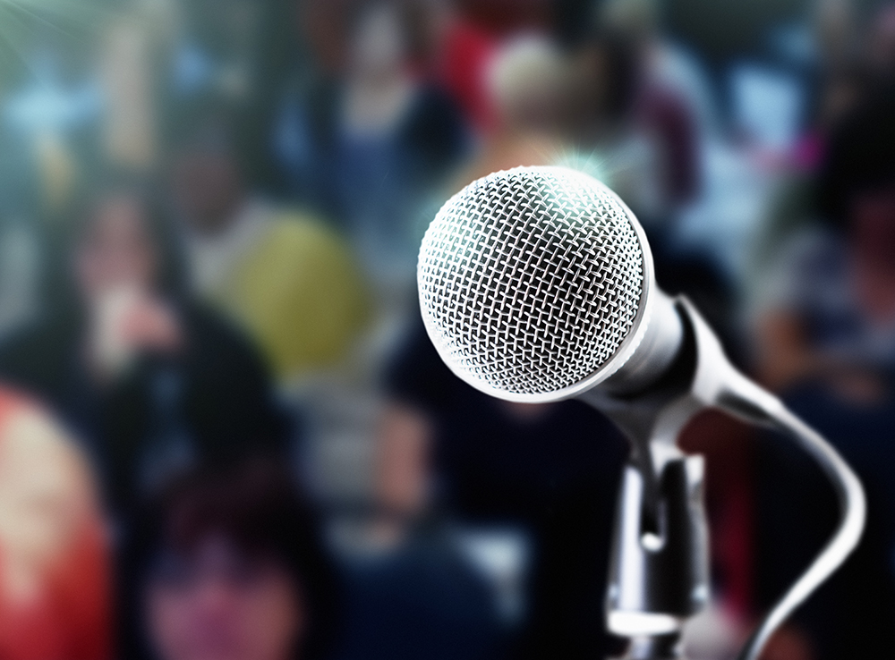 Brightly lit microphone with dark, defocused audience in the background