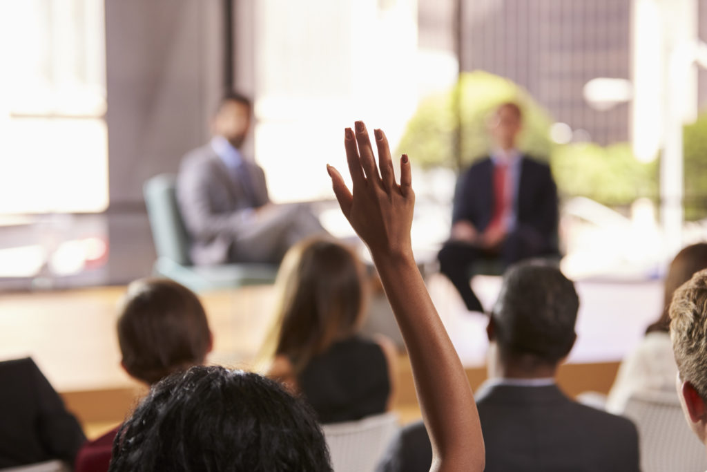 Hand in audience raised for a question at a business seminar