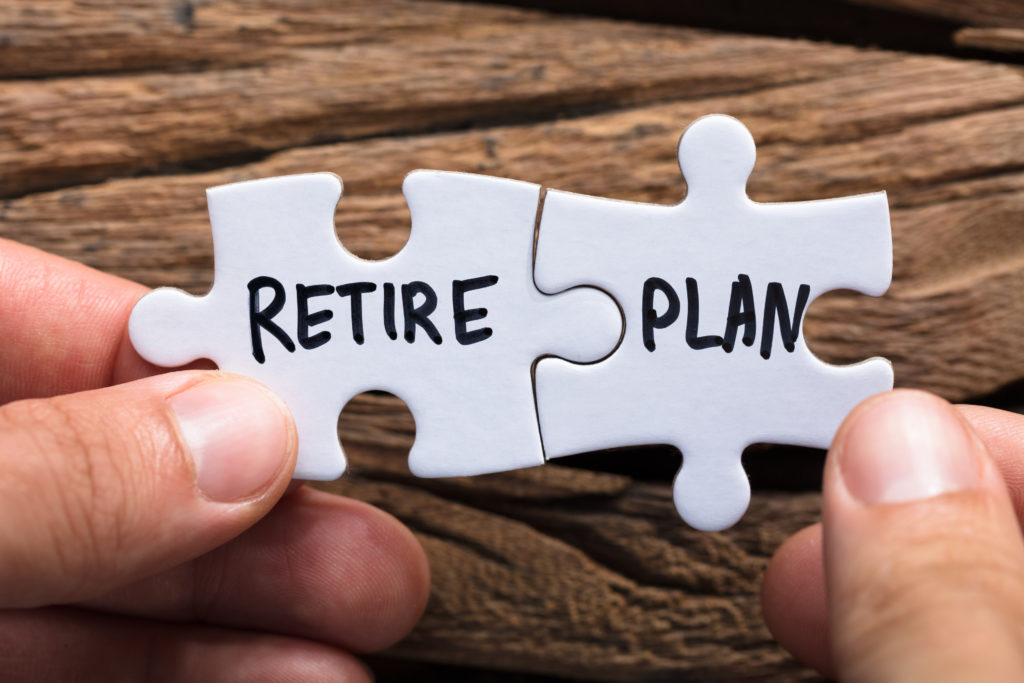 Hands Holding Retire Plan Matching Jigsaw Pieces